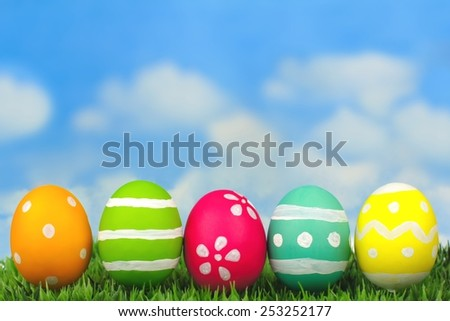 Colorful painted Easter eggs on grass with blue sky background - stock photo