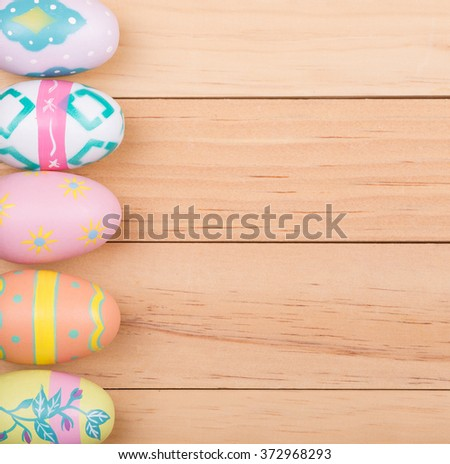 Colorful painted Easter eggs on wood background - stock photo