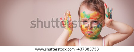 Colorful painted hands in a beautiful young girl - stock photo