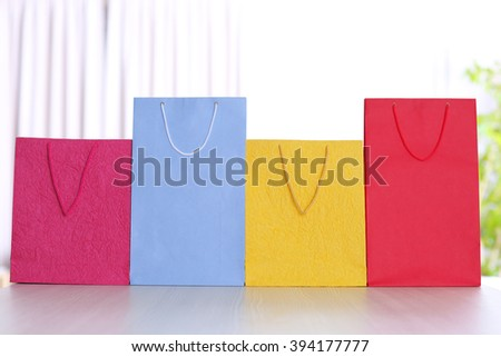 Colorful paper bags on light blurred background - stock photo