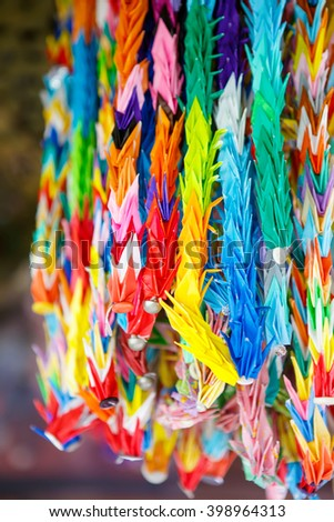 Colorful paper crane birds hanging together using fishing lines. Japanese origami in a temple in Japan. - stock photo