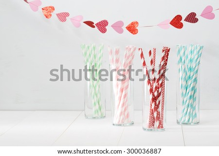 Colorful paper straws with a decorative garland of hearts symbolic of love to celebrate a party for a festive romantic occasion, with copyspace for your invitation or greeting - stock photo