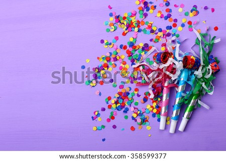 Colorful party blower on a purple background with confetti - stock photo
