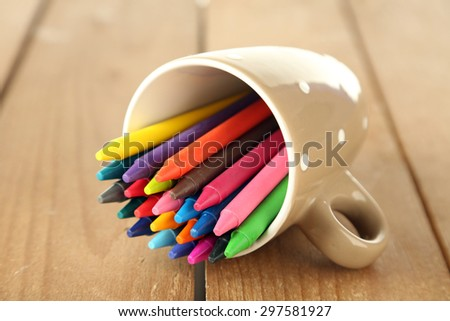 Colorful pastel crayons in cup on wooden background - stock photo