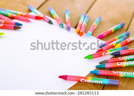 Colorful pastel crayons with white sheet of paper on wooden table, closeup - stock photo
