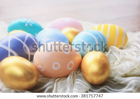 Colorful pastel easter eggs on fabric with copy space, vintage filter tone - stock photo