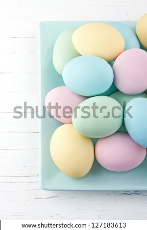 Colorful pastel easter eggs on white wooden background - stock photo
