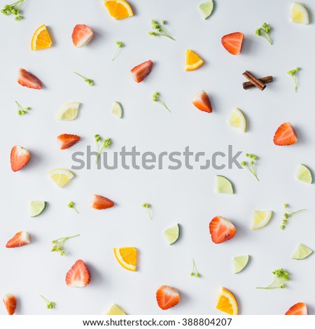 Colorful pattern made of citrus fruits, leaves and strawberries. - stock photo