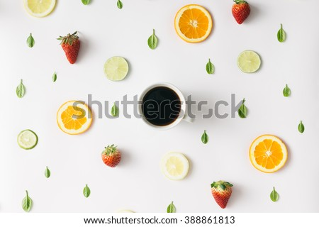 Colorful pattern made of citrus fruits, leaves and strawberries with cup of coffee - stock photo