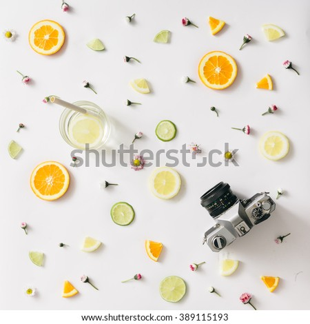 Colorful pattern made of orange, lemon, lime and flowers with lemonade and vintage camera - stock photo