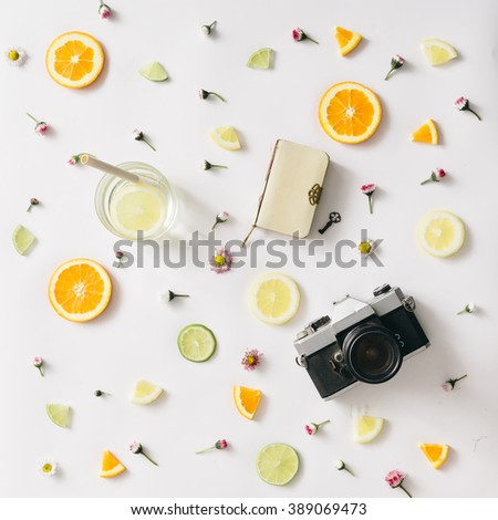 Colorful pattern made of orange, lemon, lime and flowers with lemonade and vintage camera and notebook. - stock photo