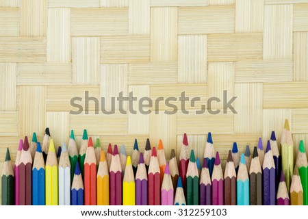Colorful pencil crayons onbamboo weave - stock photo