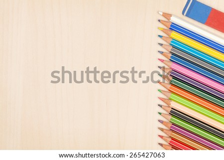 Colorful pencils and eraser over wooden office table with copy space - stock photo