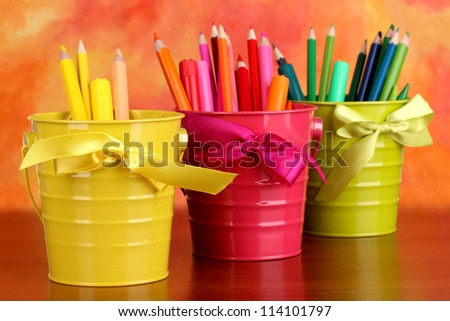 Colorful pencils and felt-tip pens in pails on color background - stock photo