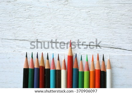 Colorful pencils background on wooden floor - stock photo