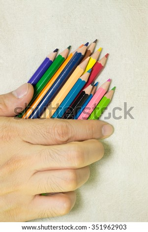 Colorful pencils in hand.on the mulberry paper cream tone. - stock photo