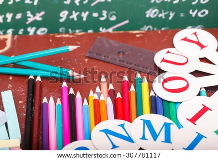 Colorful pencils of red yellow orange violet purple pink green and blue in stationary cup ruler and fan english alphabet standing on school desk on written with white chalk blackboard, horizontal - stock photo