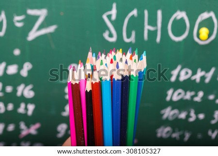 Colorful pencils of red yellow orange violet purple pink green and blue in stationary cup standing on school desk on written with white chalk blackboard background, horizontal picture - stock photo