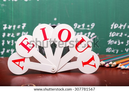 Colorful pencils of red yellow orange violet purple pink green and blue near stationary cup and fan english alphabet standing on brown school desk on written with white chalk blackboard on math - stock photo