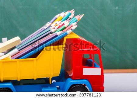 Colorful pencils of red yellow orange violet purple pink green blue chalk and fan english alphabet in plastic truck car toy standing on white school desk on blackboard backdrop, horizontal photo - stock photo