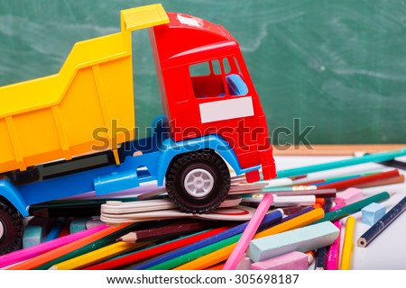 Colorful pencils of red yellow orange violet purple pink green blue chalk fan english alphabet and truck car toy lying on white school desk on blackboard background, horizontal photo - stock photo