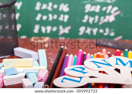 Colorful pencils of red yellow orange violet purple pink green blue ruler chalk and fan english alphabet lying on brown school desk on written with white chalk blackboard, horizontal photo - stock photo