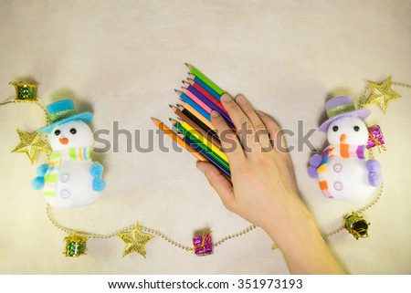 Colorful pencils on hand and Snowman and Christmas decorations on the mulberry paper cream tone. - stock photo