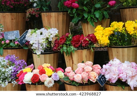 Colorful peony, roses and other flowers at the entry to flower shop in Paris (France). Selective focus. - stock photo