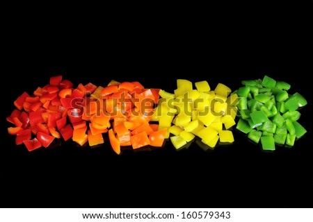 Colorful peppers diced on black background. - stock photo