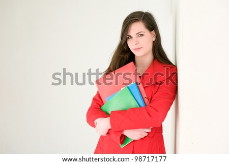 Colorful personality, portrait of a cute confident young student girl in red coat. - stock photo