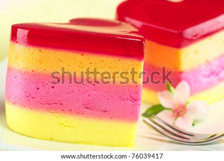 Colorful Peruvian heart-shaped jelly-pudding cakes called Torta Helada with a peach blossom and a fork on the plate (Selective Focus, Focus on the front surface of the left cake) - stock photo