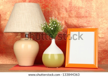 Colorful photo frame, lamp and flowers on wooden table on red background - stock photo