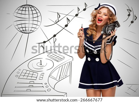 Colorful photo of a clubbing fashionable pin-up sailor girl at the nightclub with big vintage unplugged music headphones on grey sketchy background of a DJ mixer and disco ball. - stock photo