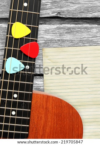 colorful picks on acoustic guitar, on old wood texture background - stock photo
