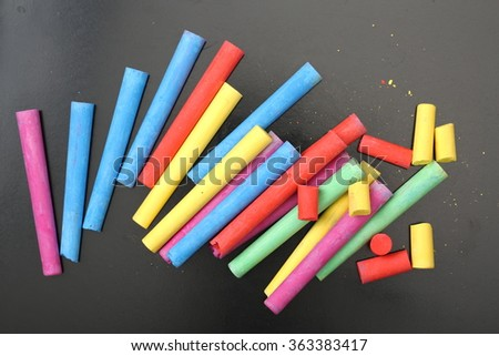 colorful pieces of chalk.on black background - stock photo