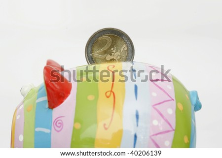 Colorful Piggy bank with a coin, closeup - stock photo