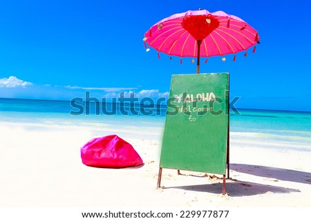 colorful pillows and bright umbrella on tropical sea and beach background, vacation in tropics, welcome sign to beach restaurant - stock photo