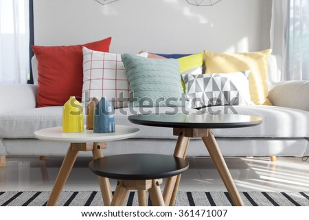 Colorful pillows on a sofa with little vase in foreground - stock photo