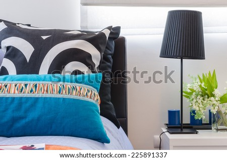 colorful pillows on bed in bedroom - stock photo