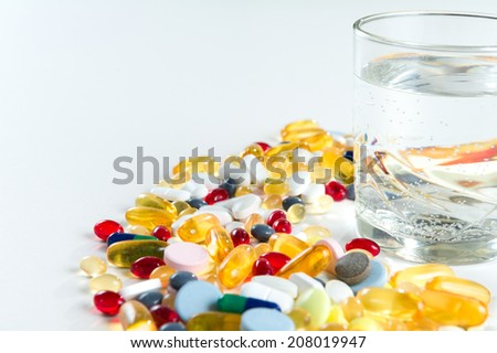 Colorful pills and glass of water, on white background - stock photo