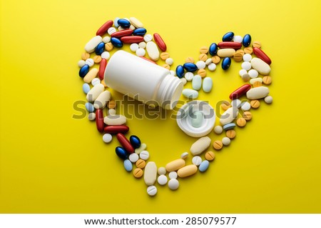 Colorful pills and tablets in shape of heart - stock photo