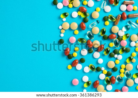 Colorful pills on blue background - stock photo