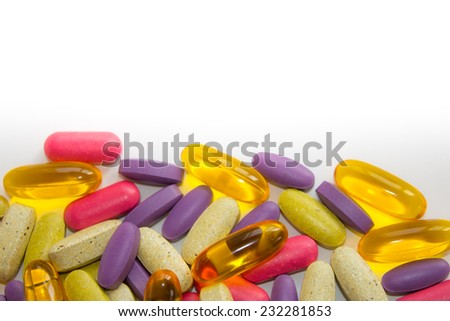 Colorful pills on white background with copy space - stock photo
