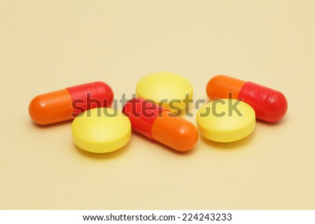 Colorful pills on yellow background - stock photo