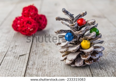 Colorful pine cone decoration with red balls on wooden table - stock photo