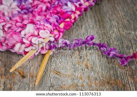 Colorful pink and purple knitting and wooden needles on rustic background - stock photo