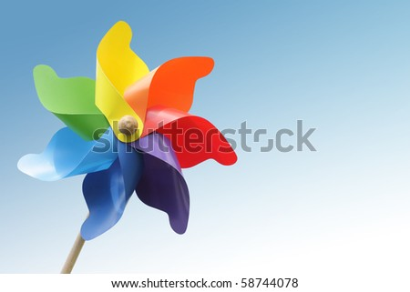 Colorful pinwheel against blue gradient background - stock photo