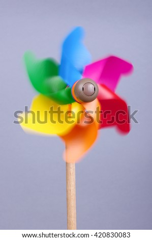 Colorful pinwheel in motion isolated on the gray background - stock photo
