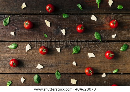 Colorful pizza ingredients pattern made of cherry tomatoes, basil and cheese on wooden background. Cooking concept. - stock photo