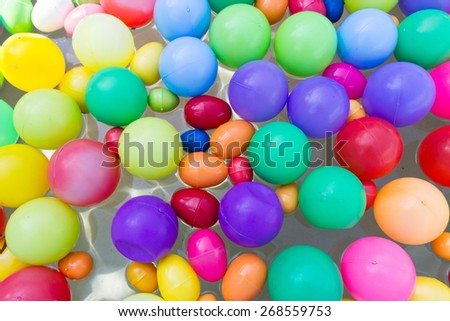 colorful plastic ball floating on water in the pool for games - stock photo